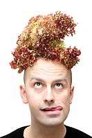 Young man contemplating on whether to eat the lettuce on top of his head or not. Isolated against a white background