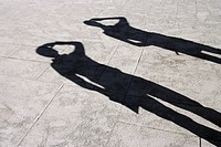 Shadows on a marble surface of two people scouting for something