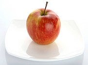 The ripe red apple lays on a white plateThe ripe red apple lays on a white plate