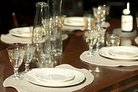 Close_up of stem glasses and plates on a dining table