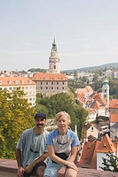 Couple sitting with Krumlov Chateau and Round Tower in background