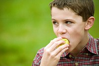 Close_up of a boy eating a fruit