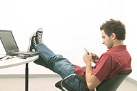 Relaxed Man with Feet on Computer Desk