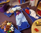 Children Napping On Floor Of Preschool Classroom