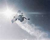 Snowboarder in mid air with snow trail