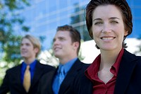Three business people stand together while the businesswoman smiles and looks ahead