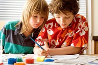 Boy painting with a paintbrush and a boy sitting beside him