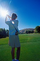 Rear view of a young woman playing golf