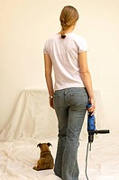 Rear view of a young woman holding an electric drill machine (thumbnail)