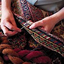 Close_up of a woman's hand sewing a woolen rug
