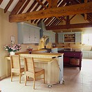 View of a country style kitchen with wooden beams overhead