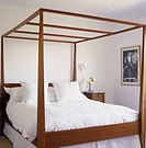 Close_up of a four poster bed with white linen