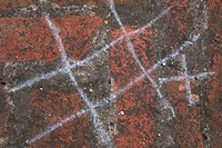 Close_up of a game of tic tac toe made with chalk on a wall