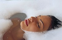 Young woman taking a bubble bath