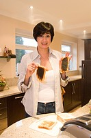 Mid adult woman holding burnt toast in a domestic kitchen