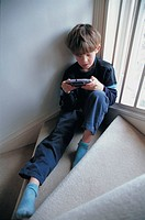kid playing video game on the staircase