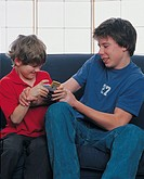 two boys fighting over a video game