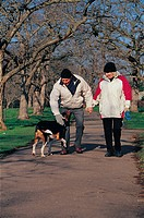 elderly couple walking their dog