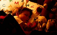 Little boy sleeping with his toys
