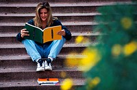 woman sitting on steps and reading