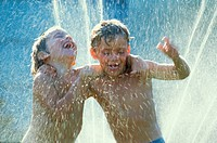 kids playing under a sprinkler