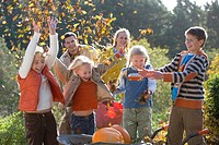 Happy, playful family throwing autumn leaves on each other