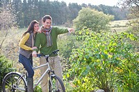 Smiling couple in countryside with bicycle