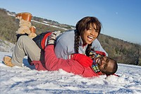 Husband and wife playing in snowy field