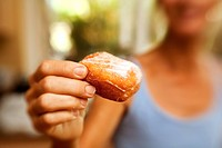 Hawaii, Maui, Wailuku, Home Made Bakery, A woman holding a fresh piece of malasada local hawaiian pastry.
