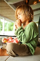 Hawaii, Kauai, Kilauea, Young boy sitting on porch eating grapefruit.