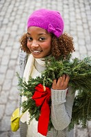 Mixed race woman carrying Christmas wreath