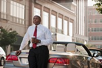 Black businessman drinking coffee near convertible