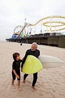 Senior Hispanic man carrying surfboards with grandson
