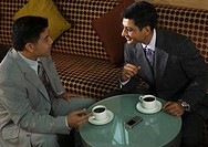 Businessmen drinking coffee together in cafe
