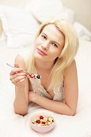 Young woman eating muesli in bed