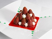 dessert of strawberries and cream and mint syrup