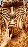 Maori carving, a tourist´s hand feels texture of face, Rotorua, New Zealand