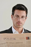Young businessman with a newspaper, portrait