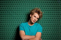 Young man in front of a green patterned wall, front view