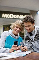 Two teenagers looking at their mobile phones, front view