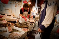Bagging up and paying for seafood at a local market in Wan Chai, Hong Kong, China