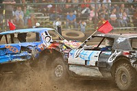 Two cars smash into each other at a demolition derby spectator event in rural Alberta Canada.