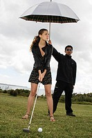 woman golfing with a man holding umbrella for her