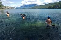 Mountain bikers crossing the Homathko River during an adventure race, British Columbia