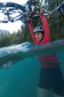 A young woman adventure racer crossing the Homathko River during a mountain biking race, British Columbia