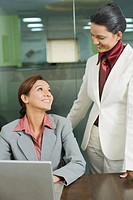 Two businesswomen working on a laptop and smiling