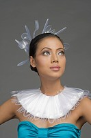 Female fashion model with neck ruff and headwear of plastic forks and spoons