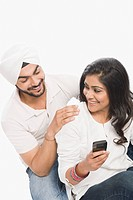Woman using a mobile phone with her husband sitting beside her