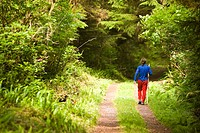 A young hiker strolls along a path, Ronning Garden, Holberg, Northern Vancouver Island, British Columbia, Canada.