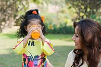 Girl drinking juice with her mother in a park